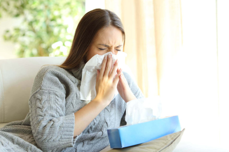 woman sneezing before removing allergens in the home