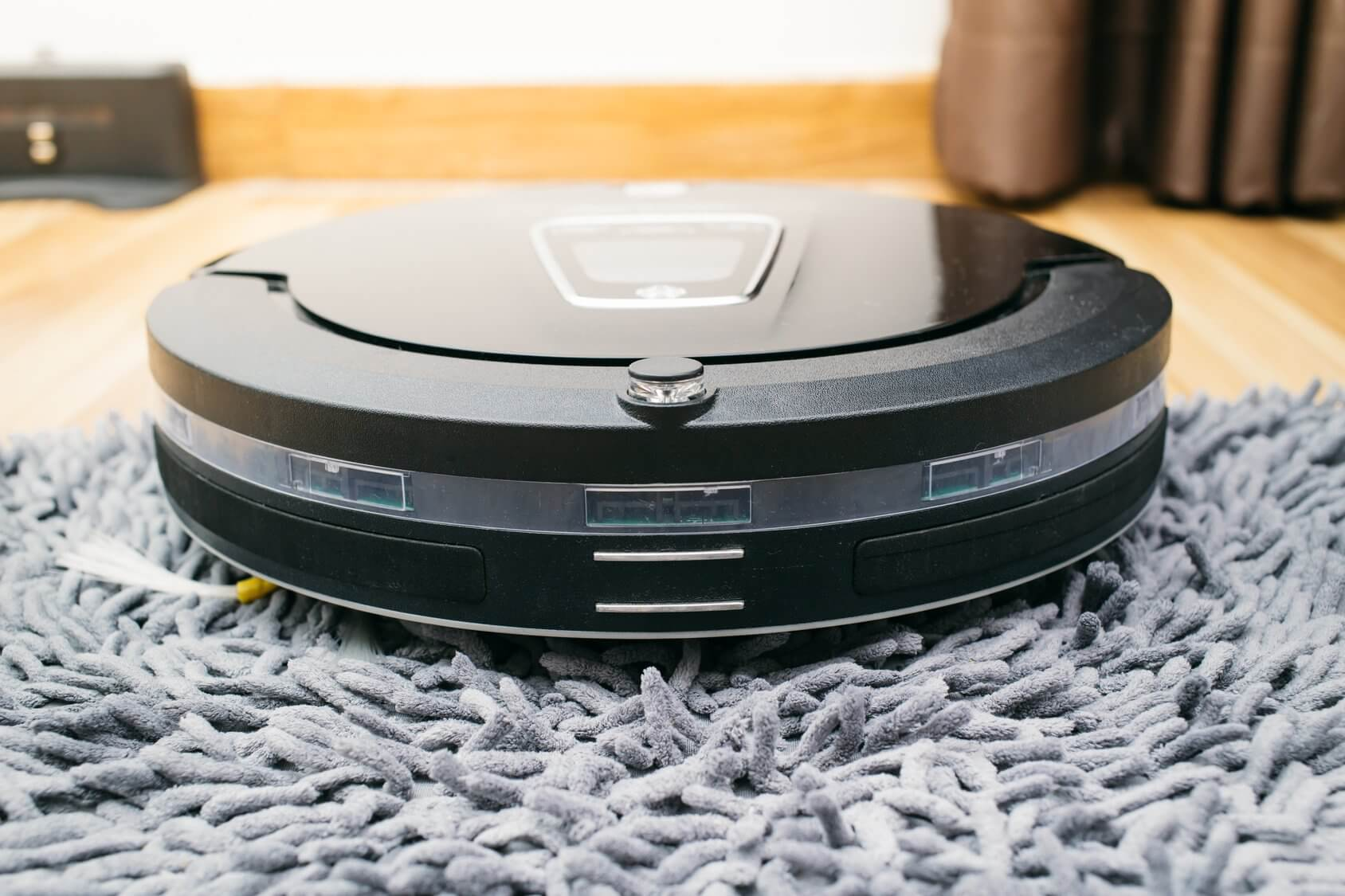 Robot vacuum cleaner on laminate wood and carpet floor, Smart robotic automate wireless cleaning technology machine in living room.